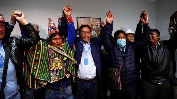 Luis Arce, al centro, candidato a la Presidencia de Bolivia por el Movimiento al Socialismo, levanta las manos en señal de victoria durante una rueda de prensa unos minutos después del lunes 19 de octubre de 2020 en La Paz.