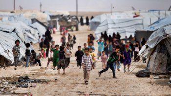 Un grupo de niños se congrega afuera de las carpas donde viven en un campamento en el que están recluidas familias de partidarios de la organización Estado Islámico en Hasakeh, Siria.