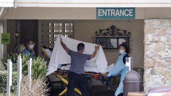 Una persona es trasladada en camilla hacia una ambulancia desde un hogar para adultos mayores en el que más de 50 personas enfermaron y esperan ser sometidas a pruebas por el COVID-19, el sábado 29 de febrero de 2020, en Kirkland, Washington.