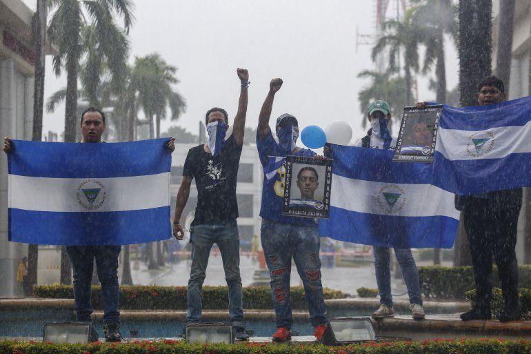 Los manifestantes sostienen banderas nacionales de Nicaragua y fotos de estudiantes asesinados durante una marcha antigubernamental denominada Nada es normal en honor a Matt Romero