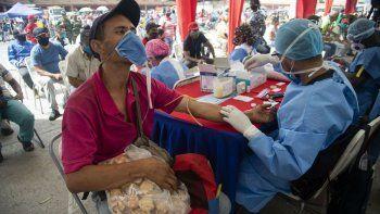 Un trabajador de salud le toma una muestra de sangre para una prueba rápida de COVID-19 a un hombre que trabaja vendiendo galletas en el mercado de alimentos de Coche en Caracas, Venezuela, el martes 23 de junio de 2020.