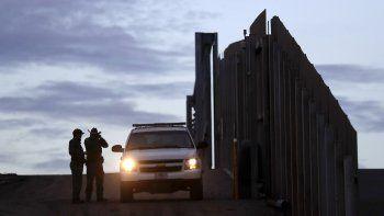 En esta imagen del 21 de noviembre de 2018, agentes de la Patrulla Fronteriza junto a uno de sus vehículos junto al muro que separa a Tijuana, México, de San Diego, en San Diego.