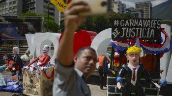 Un hombre se toma una selfie con figuras que representan al presidente Nicolás Maduro, al jefe de la Asamblea Nacional Constituyente, Diosdado Cabello y al presidente estadounidense Donald Trump en Caracas, Venezuela, el martes 25 de febrero de 2019.