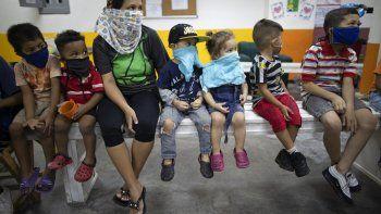 Varios niños observan una pequeña función teatral en la casa de una mujer que los asiste con las tareas escolares ahora que se imparte enseñanza a la distancia por el coronavirus en un barrio de Caracas.