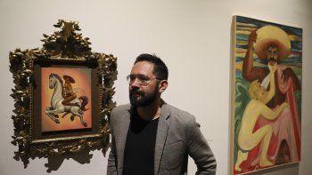 El curador mexicano Luis Vargas de pie junto a una pintura que muestra a Emiliano Zapata montando desnudo un caballo con tacones y un sombrero rosa en el Museo del Palacio de Bellas Artes el martes 10 de diciembre de 2019. La obra de Fabián Cháirez forma parte de una exhibición que recuerda al revolucionario mexicano a cien años de su muerte.