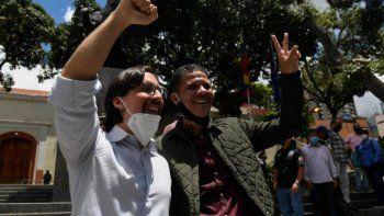 El recientemente indultado y liberado diputado opositor Gilber Caro (derecha) muestra el letrero de la Victoria junto al diputado opositor Freddy Guevara, mientras este último abandona la embajada de Chile donde se había refugiado en 2017, en Caracas.