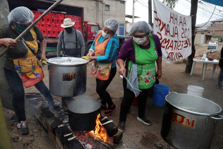 Mujeres preparan comida para un grupo de familias que enfrentan dificultades por la pandemia del nuevo coronavirus en Villa María del Triunfo en Lima