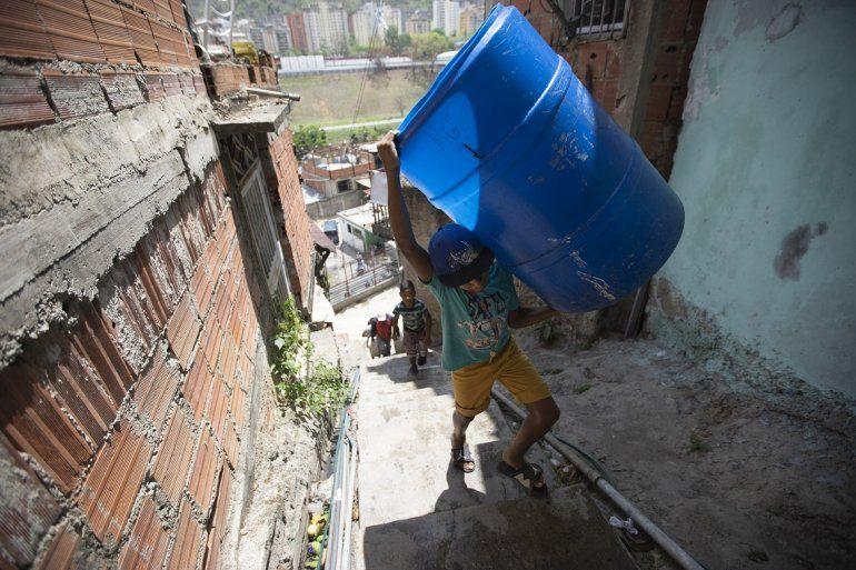 Un niño sube unas escaleras cargado con dos recipientes vacíos que llenará con el agua suministrada por un camión cisterna del gobierno