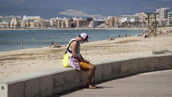 Un turista mira su teléfono en la playa de Palma en Palma de Mallorca el 29 de marzo de 2021. Las reservas para las Baleares aumentaron después de que Berlín a mediados de marzo dejó de exigir a las personas que regresaban de la región a la cuarentena debido a la baja tasa de infección en el archipiélago, que ha sido durante mucho tiempo popular entre los alemanes.