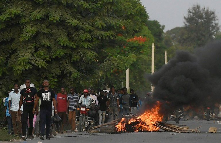Varios hombres caminan junto a una barricada en llamas después de que cientos de trabajadores huyeran de una zona en la que se llevaron a cabo manifestaciones que se tornaron violentas cerca de la ciudad natal del difunto presidente Jovenel Moise.