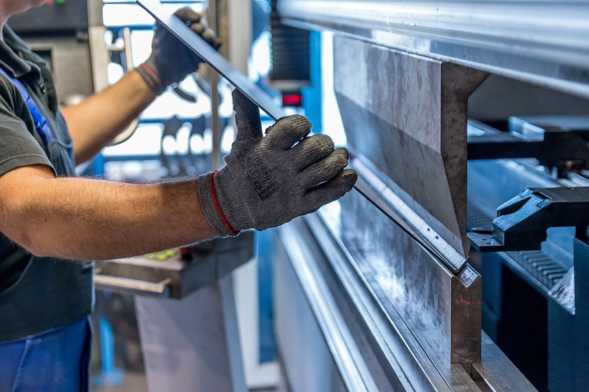 Un empleado trabaja con láminas de acero.