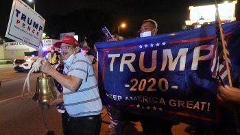 En esta fotografía del 3 de noviembre de 2020, Rafael Fagundo toca una campana mientras él y otros simpatizantes del presidente Donald Trump corean consignas y ondean banderas frente al restaurante cubano Versailles la noche de las elecciones en el vecindario Pequeña Habana de Miami.