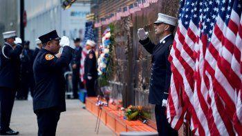 En esta imagen del 11 de septiembre de 2018, bomberos de la ciudad de Nueva York saludan frente a un monumento ubicado a un costado de un cuartel de bomberos aledaño a One World Trade Center y el Monumento al 11 de Septiembre, durante la ceremonia por el aniversario de los ataques terroristas en Nueva York.
