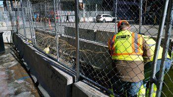 Varios trabajadores instalan alambre de navajas entre barreras en los alrededores del Centro de Gobierno del condado de Hennepin, el miércoles 23 de febrero de 2021, en Minneapolis, como parte de las medidas de seguridad en preparación para el juicio del expolicía de Minneapolis Derek Chauvin, acusado de matar a George Floyd durante un arresto en mayo pasado en Minneapolis.