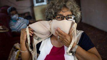 Idania Española, de 63 años, posa para una foto que muestra un sostén que adaptará en dos máscaras faciales, en medio de la propagación del nuevo coronavirus en Cojímar, Cuba, al este de La Habana, el martes 31 de marzo de 2020.