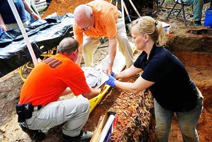 Los operarios del Sistema de Respuesta de Operaciones de Emergencias de la Morgue Jason Byrd (i) y Larry Bedores (c) ayudan a la profesora asistente de la Universidad del Sur de Florida
