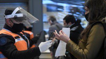 La policía verifica la identificación y el permiso de los viajeros para circular en la estación de trenes de Constitución el primer día de una cuarentena más estricta para frenar la propagación del COVID-19 en Buenos Aires, Argentina, el miércoles 1 de julio de 2020