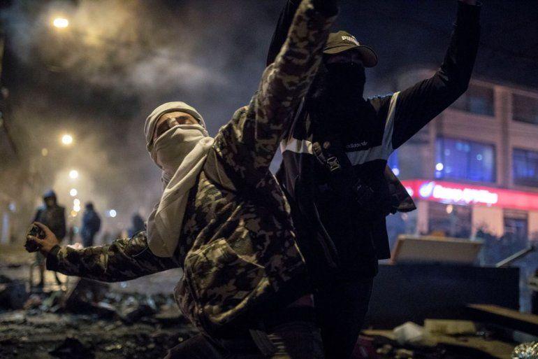 Un hombre con máscara y capucha arroja piedras a la policía el jueves 10 de septiembre de 2020 durante protestas por la muerte de un hombre a manos de la policía