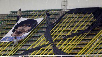 Trabajadores instalan una pancarta con la imagen del fallecido Diego Armando Maradona en el estadio Norberto Tomaghello antes del partido por la Copa Sudamericana entre el argentino Defensa y Justicia y el brasileño Vasco Da Gama, en Buenos Aires, Argentina, el jueves 26 de noviembre de 2020.