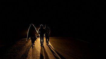 El migrante venezolano Rubi Alexander G. (L) y amigos caminan bajo temperaturas frías de noche por la carretera que une Colchane con Iquique, luego de cruzar desde Bolivia, en Huara, Chile, el 17 de febrero de 2021. Cruzando las tierras altas de la frontera entre Bolivia y Chile a pie es la parte más difícil del viaje que atraviesan los migrantes venezolanos en su camino hacia Iquique o Santiago.