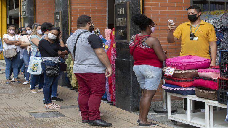 Personas con cubrebocas hacen fila antes de que una persona les tome la temperatura para entrar en una tienda en el distrito comercial del centro de Sao Paulo