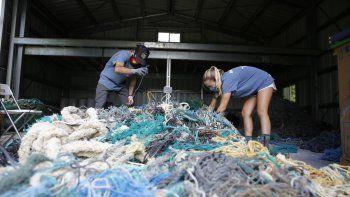 Drew McWhirter (izq) y Raquel Corniuk tratan de desenredar una enorme madeja de redes de pescadores en el Centro de Investigación de Desechos Marinos de la Universidad del Pacífico de Hawái en Kaneohe, Hawái, el 12 de mayo del 2021.