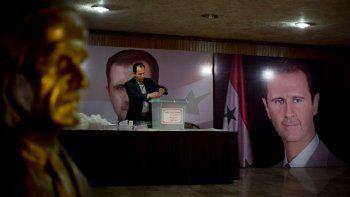 En esta imagen de archivo del 13 de abril de 2016, un funcionario sirio espera a los votantes en un centro electoral, junto a carteles del presidente, Bashar Assad, durante las elecciones parlamentarias en Damasco, Siria.