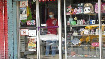 Un hombre con una máscarilla para protegerse de un posible contagio por coronavirus limpia la ventana de una tienda en el barrio China Town en la Ciudad de Panamá, el jueves 12 de marzo de 2020.