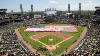 Una bandera de EEUU cubre parte del terreno de juego de los Medias Blancas de Chicago durante las ceremonias del 4 de julio (Día de la Independencia de EEUU) del 2019, antes de un juego con los Tigres de Detroit.