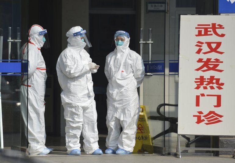 Fotografía de archivo del 28 de enero de 2020 de personal médico en trajes protectores esperando en la entrada de una clínica a que lleguen pacientes con fiebre y pacientes de Wuhan en Fuyang