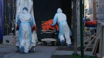 Los cuerpos de personas fallecidas por coronavirus son trasladados a un camión frigorífico que sirve como depósito temporal de cadáveres fuera del Hospital Wyckoff en el distrito de Brooklyn el 4 de abril de 2020, Nueva York.