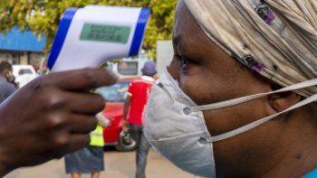 Una mujer, con mascarilla para protegerse del coronavirus, se somete a un control de temperatura antes de entrar a una tienda de comestibles, en el vecindario de Tembisa, Johannesburgo, Sudáfrica, el 19 de mayo de 2020.