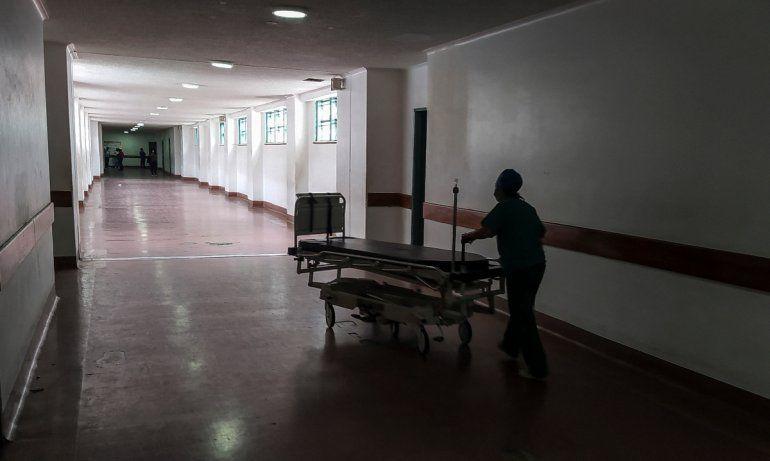 Un trabajador de la salud mueve una camilla por un pasillo del Hospital Universitario