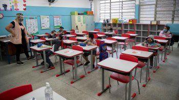 Una maestra trabaja con estudiantes, todos ellos con máscaras, durante el primer día de regreso a clases presenciales en medio de la pandemia de COVID-19 en la escuela pública Raúl Antonio Fragoso en Sao Paulo, Brasil, el lunes 8 de febrero de 2021.