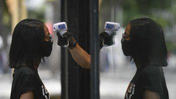 Un empleado de una tienda le toma la temperatura a una mujer como precaución contra el coronavirus el sábado 25 de julio de 2020, en Caracas, Venezuela.