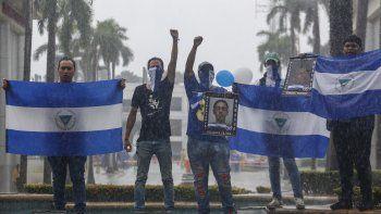 Los manifestantes sostienen banderas nacionales de Nicaragua y fotos de estudiantes asesinados durante una marcha antigubernamental denominada Nada es normal en honor a Matt Romero, en Managua, Nicaragua, el sábado 21 de septiembre de 2019.