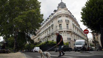 En esta foto del 13 de agosto de 2020, un hombre pasea a su perro frente a un edificio de apartamentos propiedad de Jeffrey Epstein en París. El agente de modelos Jean-Luc Brunel, quien tenía una relación estrecha con Epstein, fue arrestado el 16 de diciembre bajo sospecha de violación de menores y otros crímenes.