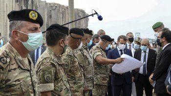 El presidente francés Emmanuel Macron, tercero desde la derecha, y el canciller francés Jean-Yves Le Drain se reúnen el martes 1 de septiembre del 2020 con fuerzas militares movilizadas para ayudar a reconstruir el puerto de Beirut.