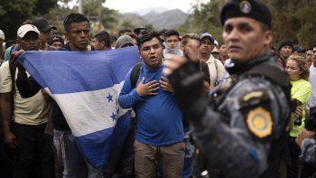 Migrantes hondureños que viajan en grupo se paran ante un policía guatemalteco, cerca de Agua Caliente, Guatemala, el 16 de enero de 2020, en la frontera con Honduras.