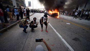 Un coche del Departamento de Policía de Atlanta arde mientras tres personas posan a pocos metros de la destrucción para una fotografía realizada durante una manifestación contra la violencia policial, el 29 de mayo de 2020, en Atlanta.