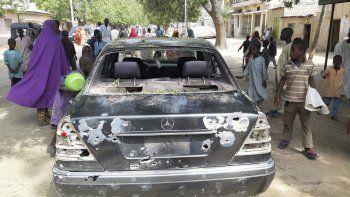 Personas observan un vehículo acribillado a tiros en el lugar de un ataque en la ciudad de Maiduguri, Nigeria, el miércoles 24 de febrero de 20021. Las autoridades dijeron que al menos 10 personas murieron y 60 resultaron heridas en el ataque.