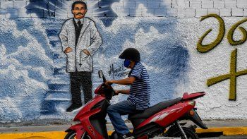 Un hombre con mascarillas pasa su motocicleta frente a un mural que representa al médico venezolano José Gregorio Hernández en una calle de Caracas, el 27 de abril de 2021. La Iglesia católica beatificará al médico venezolano José Gregorio Hernández el 30 de abril en Caracas.