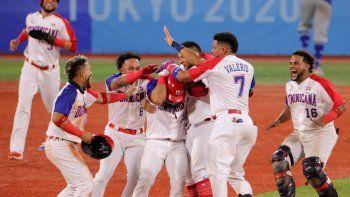 José Bautista (C) de República Dominicana es felicitado por sus compañeros luego de conectar un sencillo impulsor con durante la novena entrada del juego de repechaje de la ronda 1 de béisbol de los Juegos Olímpicos de Tokio 2020