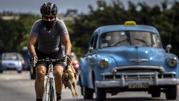 Un ciclista con máscara como medida de precaución contra la propagación del nuevo coronavirus lleva un pollo en la mano mientras pedalea su bicicleta en La Habana, Cuba, el domingo 11 de octubre de 2020.