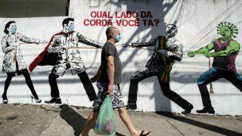 Un hombre que porta una mascarilla camina el viernes 19 de junio de 2020 frente a un mural en Sao Paulo, Brasil, que describe una lucha entre trabajadores de salud por un lado y el presidente Jair Bolsonaro y un personaje que representa al coronavirus por el otro, con un mensaje en portugués que dice: ¿De qué lado de la cuerda estás tú?