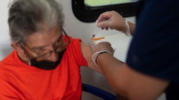 Una trabajadora de salud administra una vacuna de Johnson & Johnson contra el COVID-19 a Genaro Otero, de 71 años, el miércoles 23 de junio de 2021, durante una campaña de vacunación que forma parte de los festejos de la Noche de San Juan, en una playa pública en San Juan, Puerto Rico.