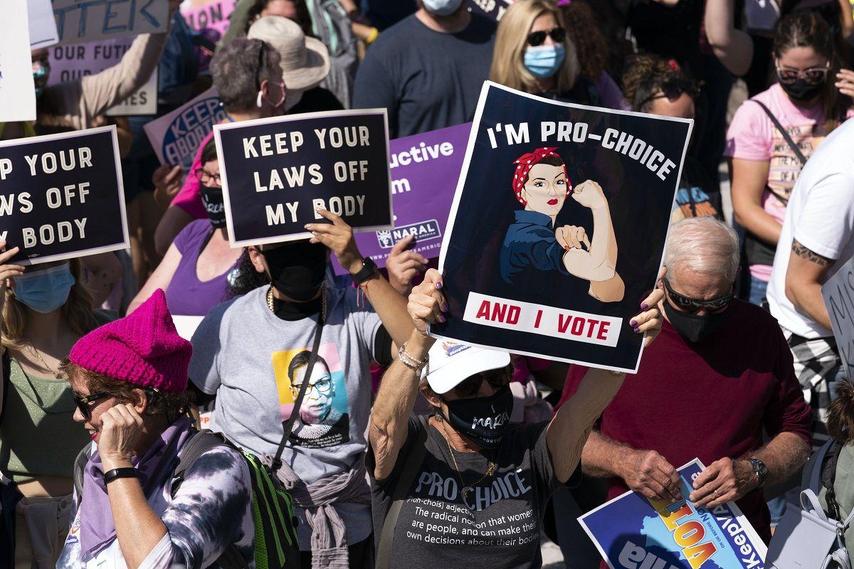 Manifestantes llevan carteles en la Marcha de Mujeres en Washington el sábado, 2 de octubre del 2021.