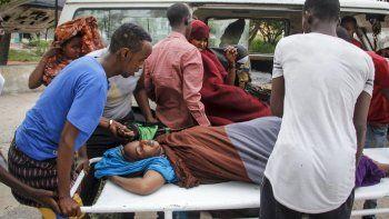 Trabajadores médicos y otros somalíes ayudan a una mujer que resultó herida cuando un coche bomba explotó frente al Hotel Elite, el domingo 16 de agosto de 2020, en Mogadiscio, Somalia.