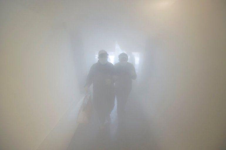 Una pareja con mascarilla pasa por una sala de descontaminación como medida de precaución contra la propagación del coronavirus antes de entrar a una tienda