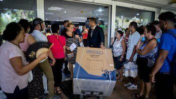 Un trabajadorlleva un congelador recién comprado mientras otras personas hacen cola en una tienda en La Habana, Cuba, el lunes 28 de octubre de 2019.